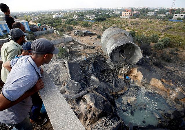 فلسطينيون يتفقدون موقعا تابعا لـ حماس بعد القصف الجوي الإسرائيلي في منطقة المغراقة، ضواحي مدينة غزة، قطاع غزة، 9 أغسطس/ آب 2018
