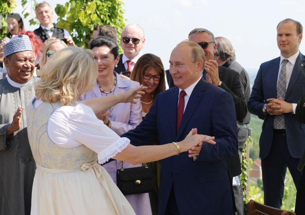 الرئيس فلاديمير بوتين خلال أداء رقصة مع وزيرة الخارجية النمساوية كارين كنايلس في حفل زفافها