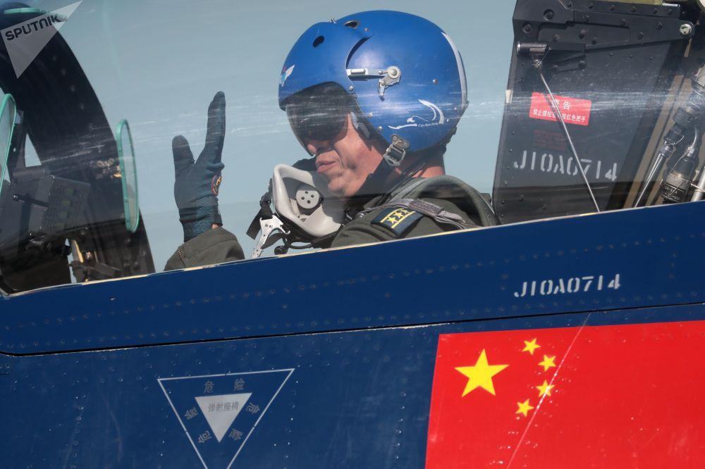 طيار لمقاتلة الجيل الرابع 6xJ-10 متعددة الأغراض التابعة لفرقة الاستعراض الجوي الأول من أغسطس الصينية بعد عرض جوي في المنتدى التقني العسكري الدولي أرميا - 2018 (الجيش - 2018 في كوبينكا