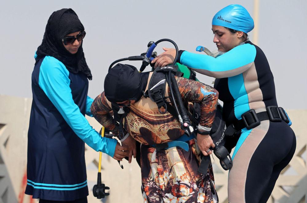 السعوديتان دانا القطري وبثينة اليوسف تساعدان زميلتهن مع أجهزة الغطس قبل بدء دروس الغطس، في شاطئ نصف القمر بمدينة الظهران، المملكة العربية السعودية، 15 سبتمبر/ أيلول 2018