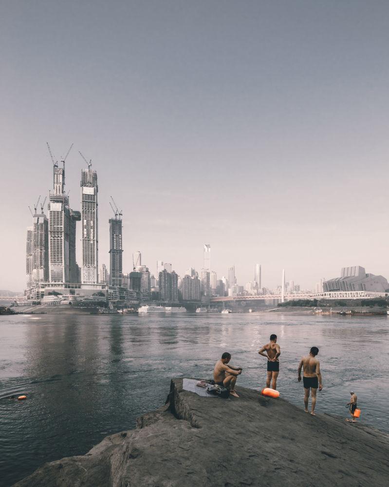 صورة لأشخاص يسبحون على خلفية ناطحات سحاب في شنغهاي Raffles City Chongqing ، من قبل المصور جيو وينكياو من الصين، الذي دخل ضمن قائمة المرشحين النهائيين لمسابقة جوائز فن التصوير المعماري 2018 في فئة حس المكان