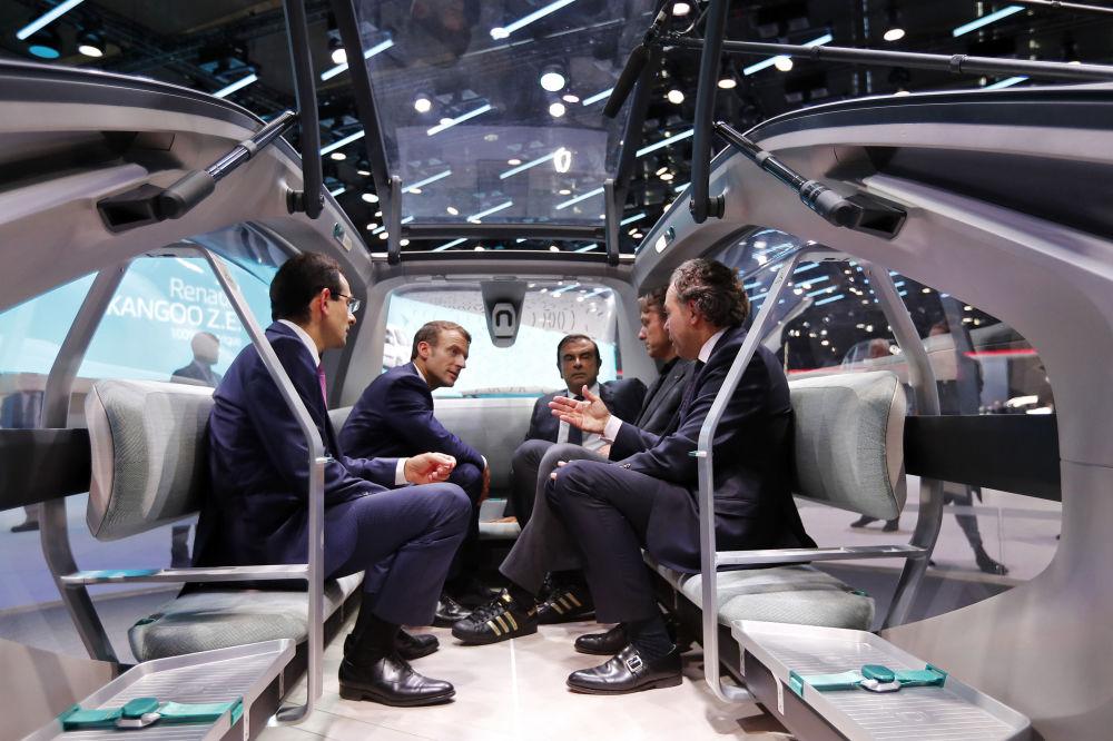 الرئيس الفرنسي إيمانويل ماكرون يجلس مع  المدير التنفيذي لشركة رينو الفرنسية كارلوس غوسن (وسط الصورة)، ويستمع إلى مدير شركة تصنيع سيارات رينو ليوك شاتيل (يمين الصورة) في باريس، 3 أكتوبر/ تشرين الأول 2018