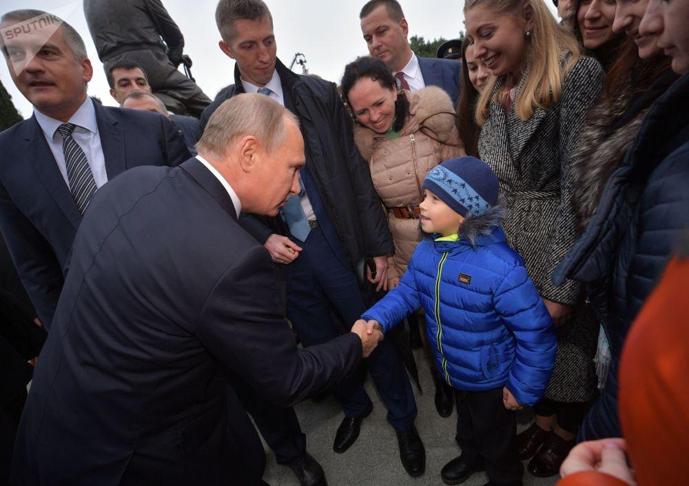 الرئيس فلاديمير بوتين يصافح على طفل أثناء لقائه مع المواطنين، بعد مراسم افتتاح نصب تذكاري للإمبراطور ألسكندر الثالث في يالطا، 18 نوفمبر/ تشرين الثاني 2018