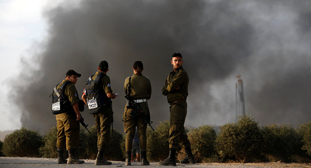 جنود إسرائيليون بالقرب من السياج الحدودي على الجانب الإسرائيلي من الحدود مع قطاع غزة واحتجاج فلسطينيين على الجانب الآخر