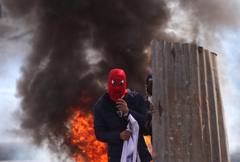 متظاهرون مقنعون من كشمير أمام عجلات مشتعلة بالقرب من موقع اشتباكات بين قوات الشرطة الهندية ومسلحين مشتبهين في سرينجار، 17 أكتوبر/ تشرين الأول 2018