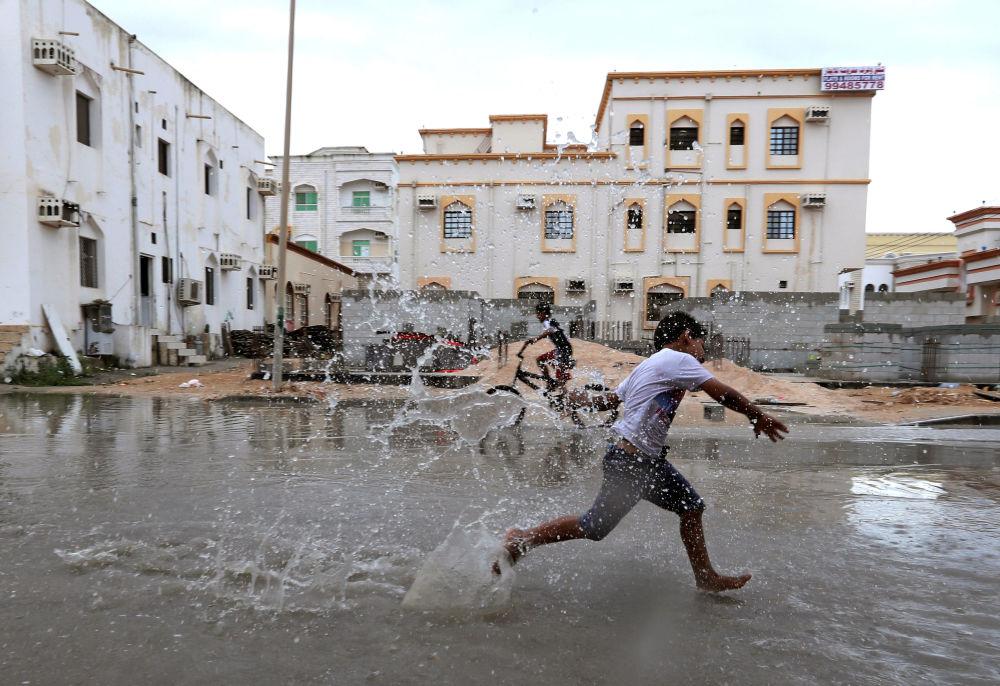 أطفال يلعبون بمياه الفياضانات بعد إعصار لبان في حي صلالة، عُمان 13 أكتوبر/ تشرين الأول 2018