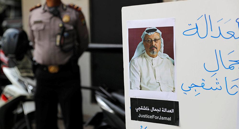 شرطي يقف حراسة بينما كان صحفي إندونيسي يحمل لافتة خلال مظاهرة احتجاج على اختفاء الصحفي السعودي جمال خاشقجي أمام سفارة المملكة العربية السعودية في جاكرتا