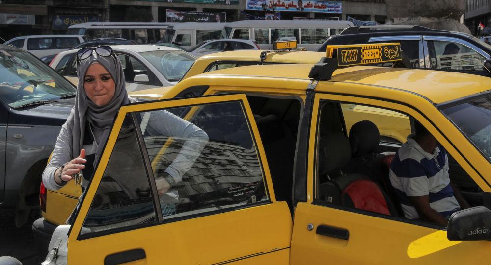 امرأة تخرج من سيارة الأجرة (تاكسي) في وسط دمشق، سوريا 16 سبتمبر/ أيلول 2018