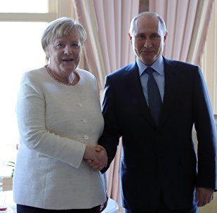 الرئيس الروسي، فلاديمير بوتين، مع المستشارة الألمانية، أنجيلا ميركل، على هامش القمة الرباعية
