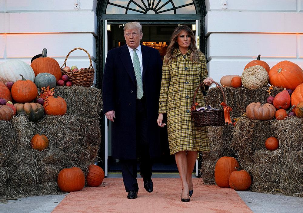 الرئيس الأمريكي دونالد ترامب وزوجته ميلانيا ترامب محاطان بالقرع العسلي والقش في البيت الأبيض احتفالا بعيد الهالوين، 28 أكتوبر/تشرين الأول 2018
