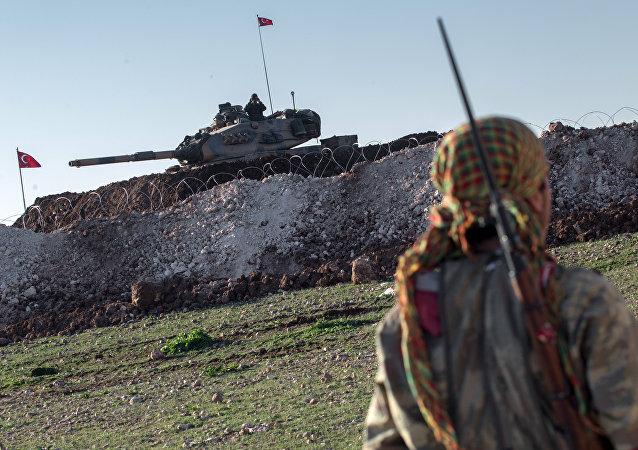 قوات وحدات حماية الشعب الكردية بالقرب من دبابة الجيش التركي، بينما يعمل الأتراك لبناء مقبرة عثمانية جديدة في قرية إسمة في محافظة حلب، سوريا، 22 فبراير/ شباط 2015