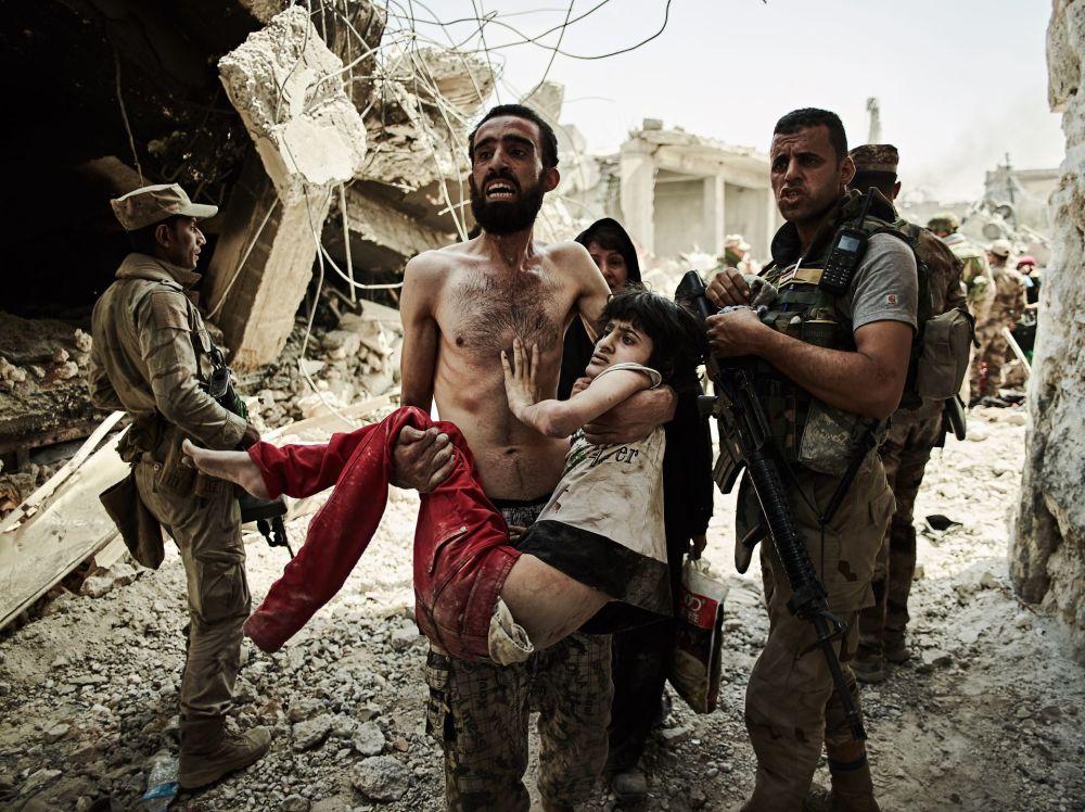 صورة بعنوان Man carries injured son، للمصور زاخ لوري، الحاصل على المرتبة الأولى في فئة رحلات ومغامرات