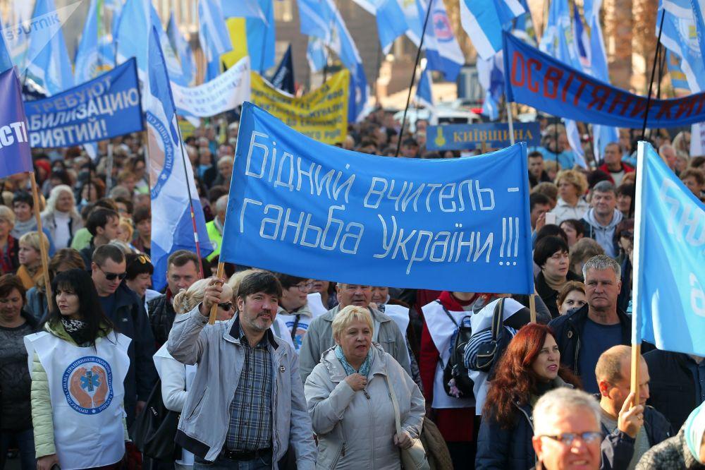 مواطنون أوكرانيون يشاركون في مظاهرة تطالب النقابة العمالية في كييف، مطالبين بزيادة الحد الأدنى للأجور
