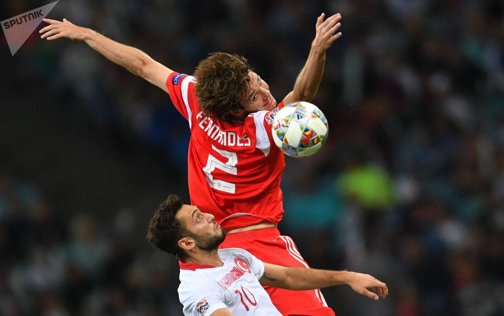 اللاعب التركي هاكان تشالهان أوغلو والروسي ماريو فرنانديز في مباراة لبطولة دوري الأمم الأوروبية  بين منتخبي روسيا وتركيا