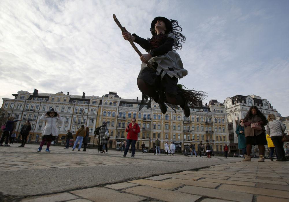 فتاة ترتدي زي ساحرة مع عصا طائرة في إطار مسيرة الزومبي الاحتفالية وسط العاصمة الأوكرانية كييف، 27 أكتوبر/ تشرين الأول 2018