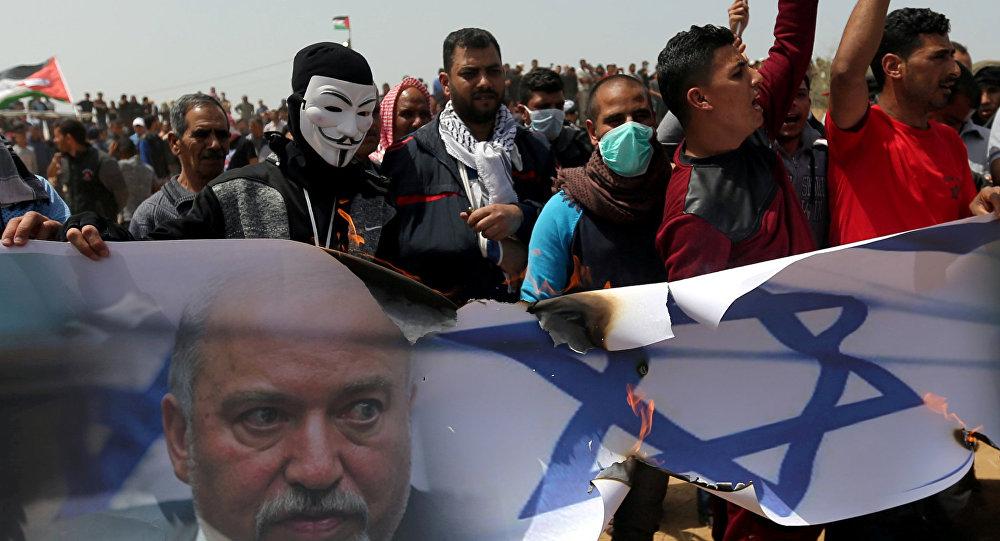 متظاهرون فلسطينيون يحرقون صورة لعلم إسرائيلي ووزير الدفاع الإسرائيلي أفيغدور ليبرمان خلال مظاهرة في جنوب قطاع غزة