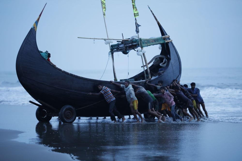 صيادون يدفعون بمركب الصيد إلى قرية الصيد شابلابور، بنغلادش 13 نوفمبر/ تشرين الثاني 2018