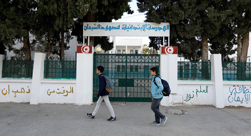أطفال يمشون أمام مدرسة مغلقة أثناء إضراب تونس
