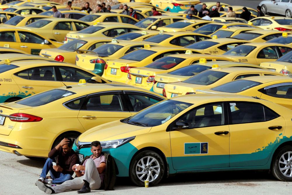 سائقو سيارات الأجرة يجلسون بجانب سيارات الأجرة الخاصة بهم خلال الاحتجاجات، خارج البرلمان في عمان، الأردن  27 نوفمبر/ تشرين الثاني  2018