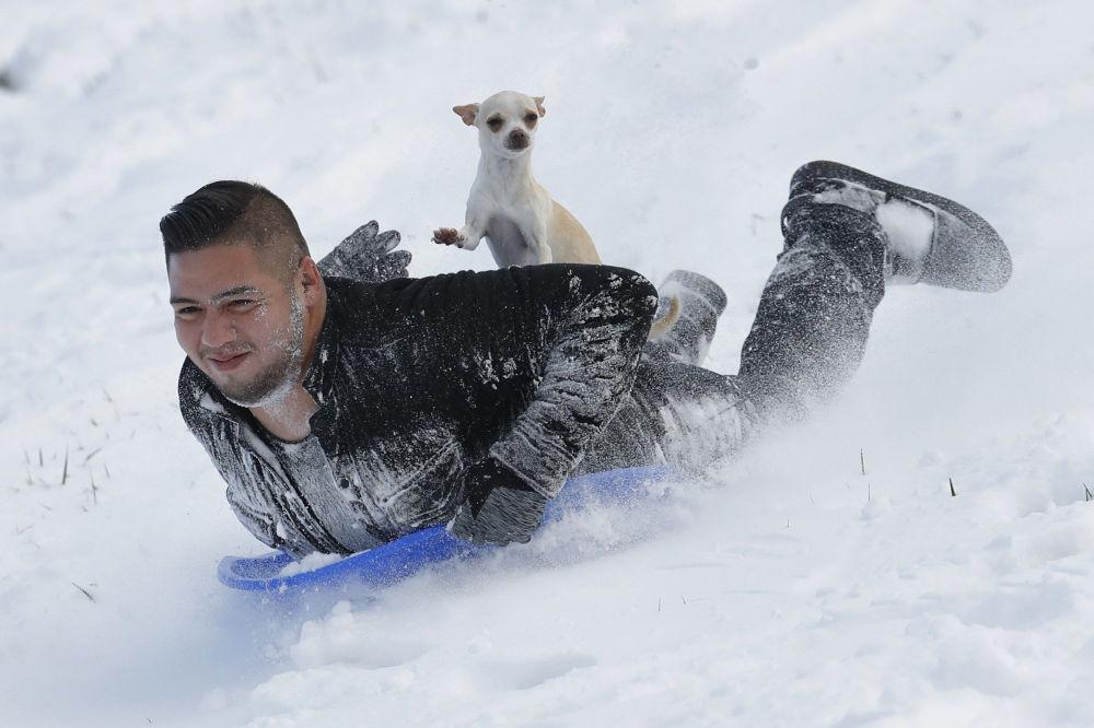 جوني ميندوزا وكلبه سوبي يتزحلق من تل جليدي في كانساس، كندا