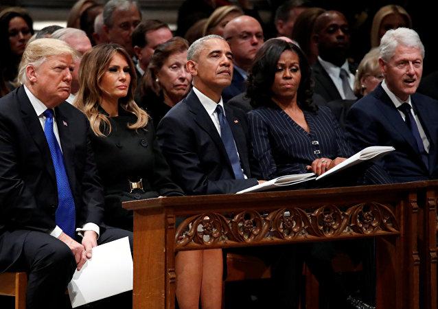 ميشيل أوباما مع زوجها باراك أوباما يجلسان بجوار ميلانيا ترامب والرئيس الأمريكي دونالد ترامب في جنازة جورج بوش الأب في كاتدرائية واشنطن الوطنية، 5 ديسمبر/كانون الأول 2018