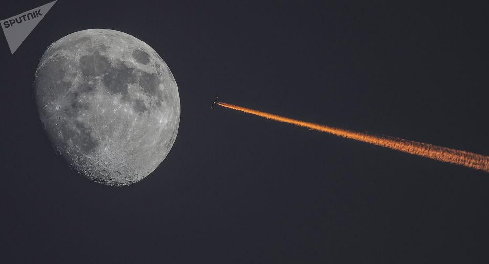 القمر والطائرة على خلفية غروب الشمس