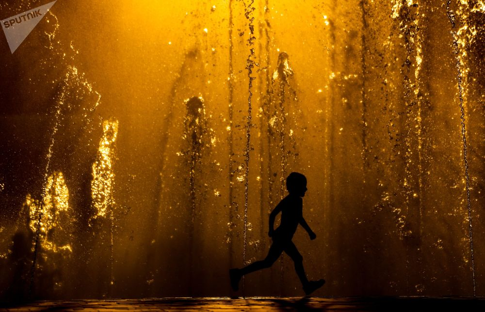 أطفال يلعبون بين نافورات المياه في يوم حار في فولغوغراد، روسيا