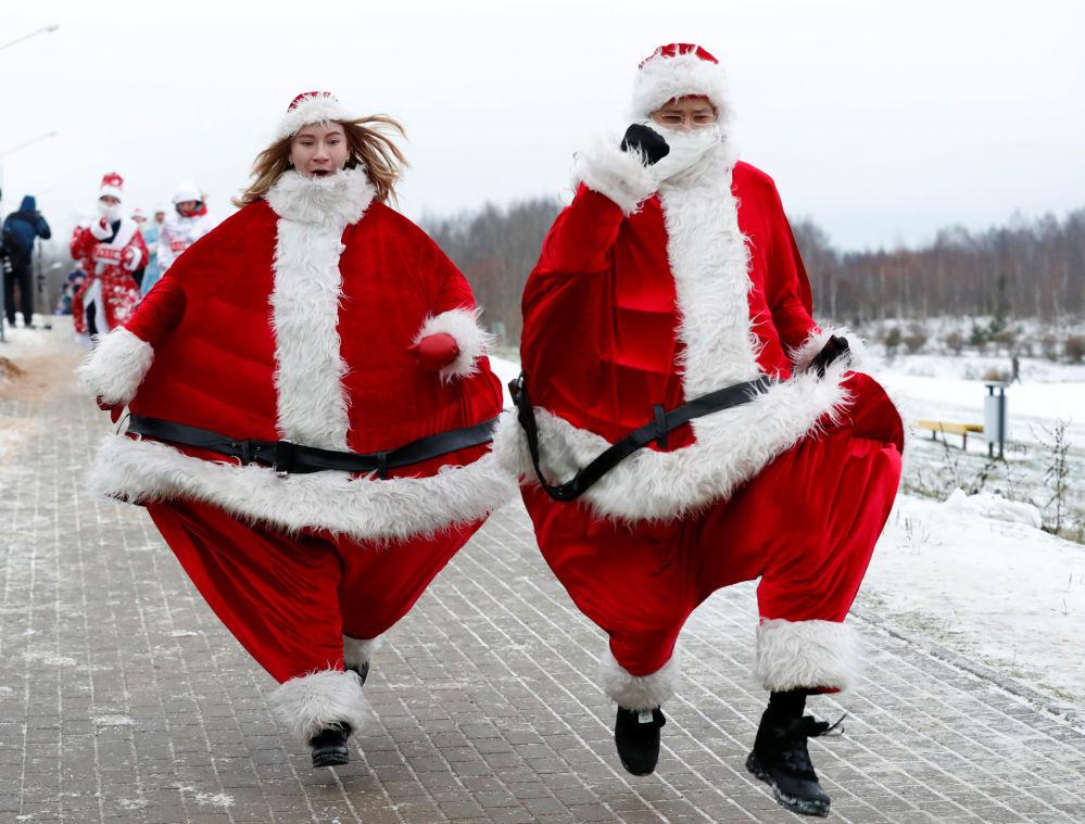 زوجان من بيلاروسيا يرتديان زي سانتا كلاوز (بابا نويل)، يشاركان في سباق سنوي حول بحيرة في مدينة مينسك، بيلاروسيا 15 ديسمبر/ كانون الأول 2018