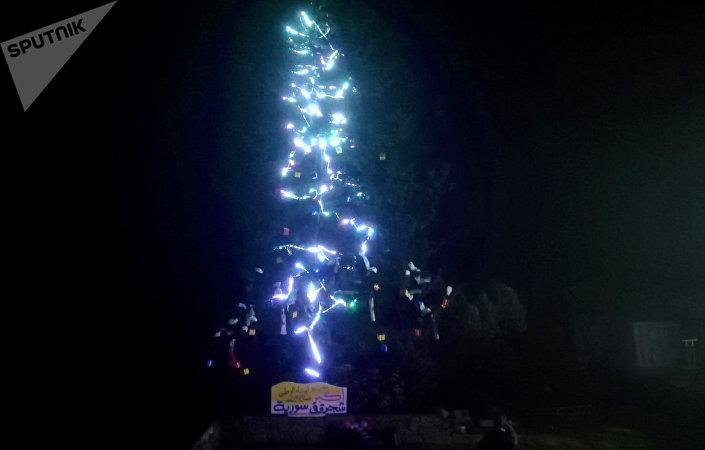 جرحى الحرب وأطفال الشهداء يضيئون أكبر شجرة طبيعية لعيد الميلاد في سوريا