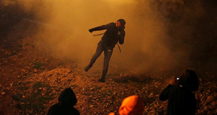 مهاجر يحاول الوصول إلى الولايات المتحدة في أثناء إلقاء قوات حماية الحدود الأمريكية الغاز المسيل للدموع على الجانب المكسيك
