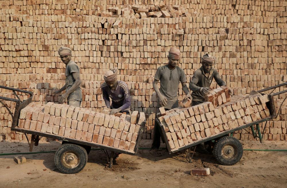 عمال مصنع الطوب يحمّلون الطوب على عربات في دكا، بنغلاديش، 9 يناير/ كانون الثاني 2019