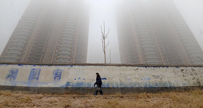 امرأة ترتدي قناعا وتسير وسط المباني في يوم ملوث في إحدى مقاطعات الصين