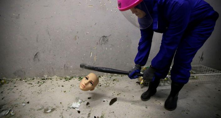 غرفة الغضب في بكين - فتاة ترتدي زيا واقيا وتقوم بتحطيم رأس تمثال، الصين 12 يناير/ كانون الثاني 2019