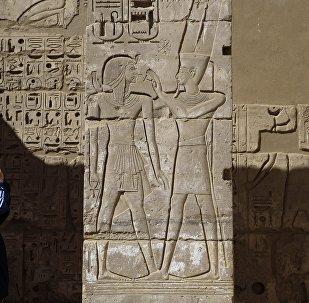 سائح يلتقط صورة لنقوش على معبد رمسيس الثالث في الأقصر