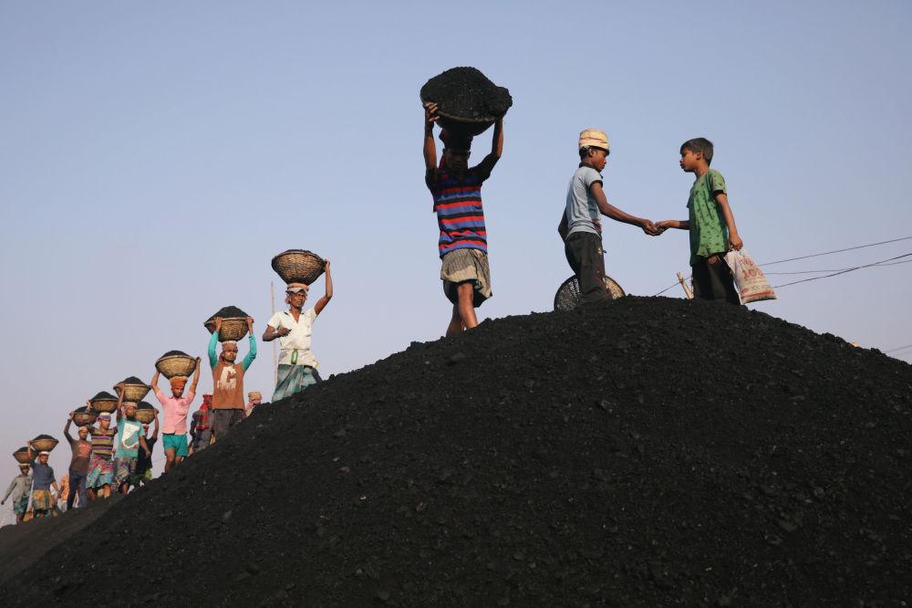 عمال الفحم في السوق وهم يفرغون عبّارة في دكا، بنغلاديش، 13 يناير/ كانون الثاني 2019
