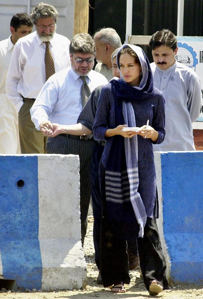 سفيرة النوايا الحسنة للمفوضية السامية للأمم المتحدة لشؤون اللاجئين، أنجولينا جولي، تسير مع مسؤولين في مركز كاشا غاري لإعادة اللاجئين إلى وطنهم خارج بيشاور، في 5 مايو/ أيار 2005.