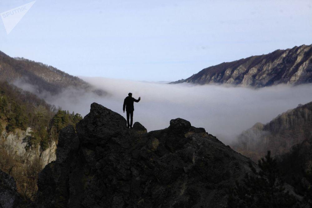 سائح يلتقط صورة ضباب فوق المنطقة الجبلية غالانتشوجسكي في الجمهورية الشياشانية