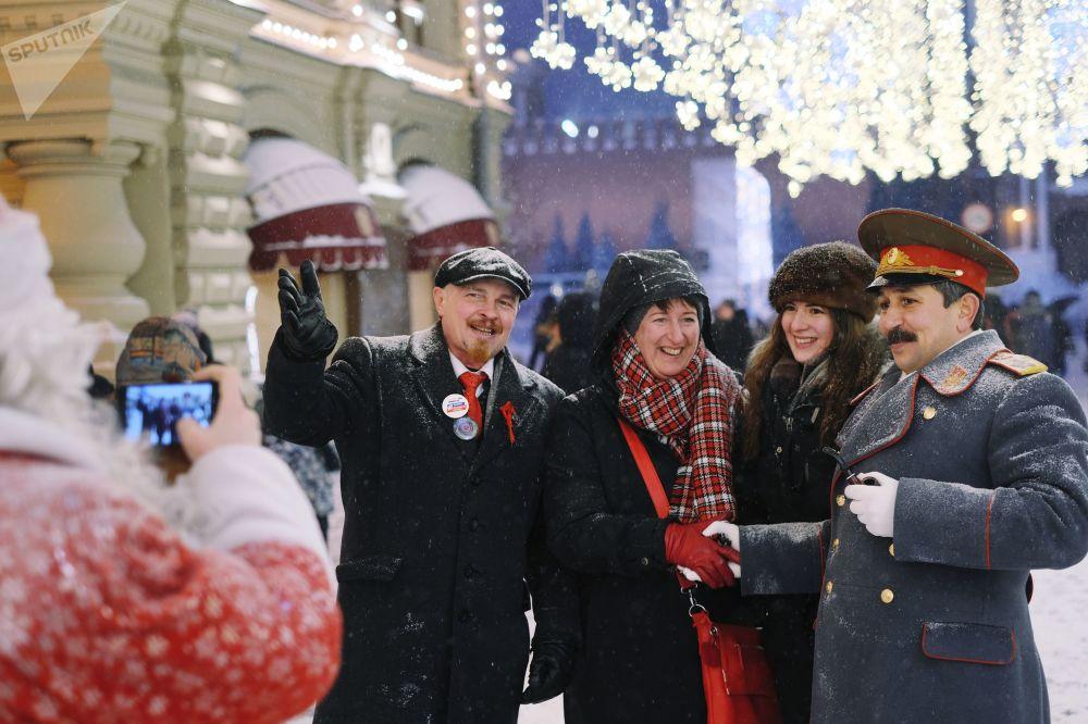 سياح في موسكو يلتقطون صورة جماعية مع رجلين يرتديان أزياء فلاديمير لينين و جوزيف ستالين خلال تساقط ثلوج في شارع نيكولسكايا بالرق من الساحة الحمراء