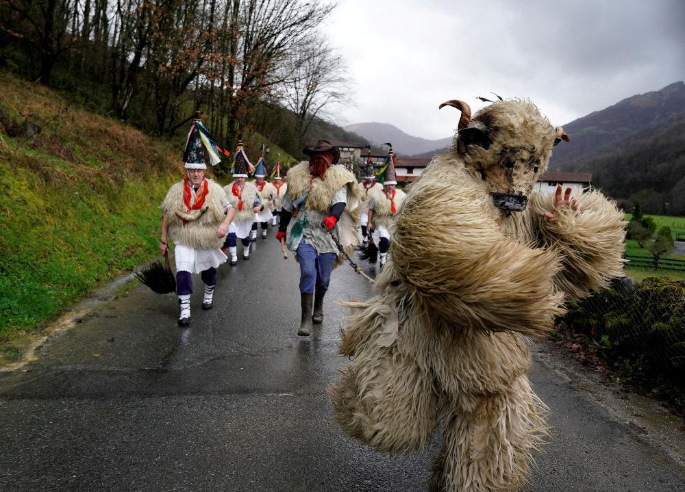 رجل يرتدي زي دب يرافق راقصين يرتدون زيا يعرف باسم جالدوناك، يمارسون طقسا لدرء الأرواح الشريرة ويوقظون الربيع المقبل، خلال احتفالات الكرنفال في إيتورين، شمال إسبانيا في 28 يناير/ كانون الثاني 2019