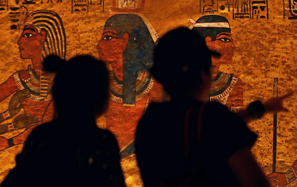الزائرون ينظرون إلى الرسومات المصرية القديمة على الجدار الذي تم تجديده حديثًا لقبر الفرعون الصغير الملك توت عنخ أمون في وادي الملوك بالأقصر