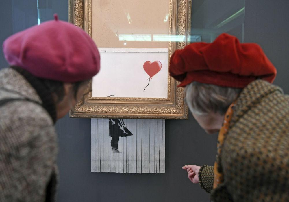ينظر الناس إلى لوحة بانكسي الممزقة الحب في الباحة (Love is in the Bin) في متحف فريدر بوردا في بادن-بادن يوم الثلاثاء الماضي 5 فبراير/ شباط 2019، حيث سيعرض العمل من 5 فبراير/ شباط إلى 3 مارس/ آذار 2019. واسم اللوحة من الأساس فتاة والبالون (A Girl With Balloon)، ومنذ أن دمرت االوحة بنفسها في مزاد فني في لندن، أطلقت عليها اسم Love is in the Bin.
