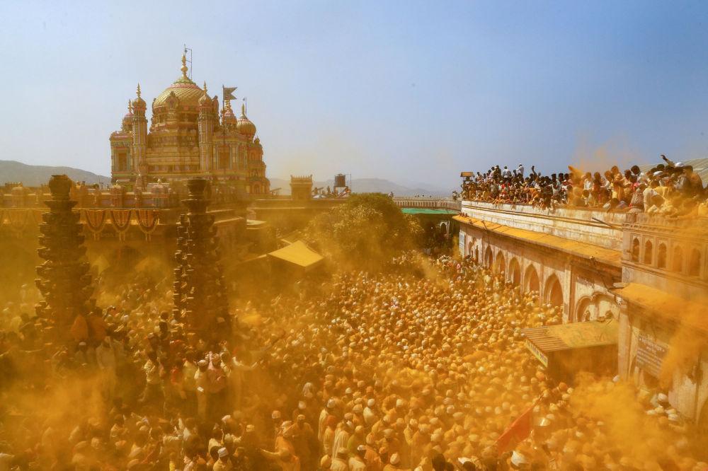 يلقي المتعبدون مسحوق الكركم كمقدمات لإله الراعي خاندوبا في حين يحمل آخرون بالكانكوين خلال الاحتفال بـ سومفاتي أمافاسيا (Somvati Amavasya) في معبد في جيجوري، الهند، 4 فبراير/ شباط 2019