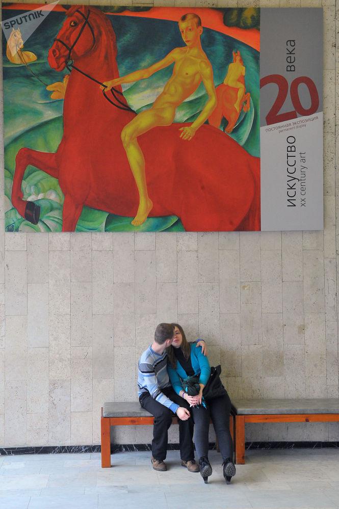 شخصان على خلفية لافتة إعلان لعرض فني بمتحف تريتياكوفسكايا في موسكو