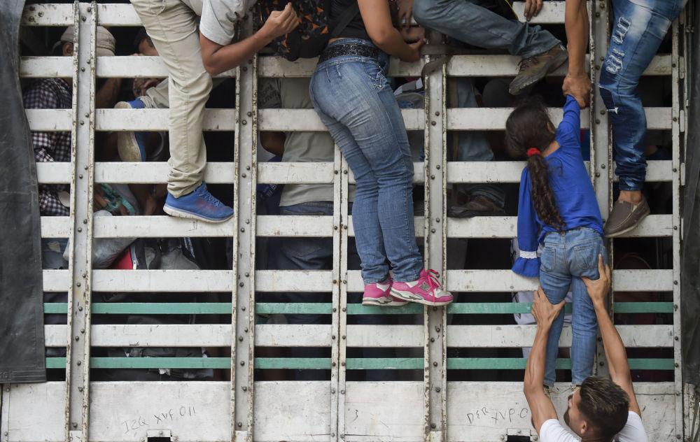 مهاجرون فنزويليون يصعدون على شاحنة على الطريق من كوكوتا إلى بامبلونا، في دائرة نورتي دي سانتاندر، كولومبيا، في 10 فبراير/ شباط 2019