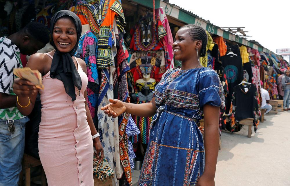 بائعات الملابس يتبادلن المال في مارينا، في العاصمة التجارية في نيجيريا لاغوس، نيجيريا في 11 فبراير/ شباط 2019