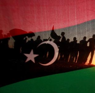 ليبيون يظهرون من خلال علم مملكة ليبيا خلال مسيرة الاحتفال أمام مقر القذافي في مجمع باب العزيزية في طرابلس