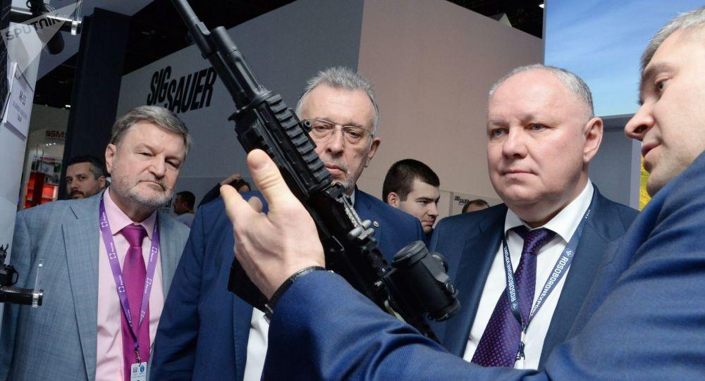المدير العام لشركة روس أوبورونن إكسبورت، الكسندر ميخييف (يسار) يتفقد بندقية كلاشنيكوف -200  ، والتي صنعتها شركة كلاشنيكوف، في معرض آيدكس 2019