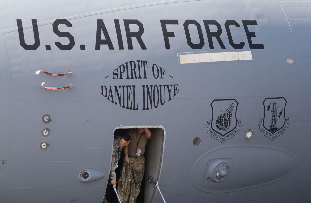 جنود أمريكيون على خلفية طائرة من طراز بوينغ إس-17أ (Boeing C-17A Globemaster III) التابعة للقوات العسكرية الأمريكية، خلال المراسم الافتتاحية للمؤتمر والمعرض العسكري آيرو إنديا 2019 (Aero India 2019) في بنغالور، الهند 20 فبراير/ شباط 2019