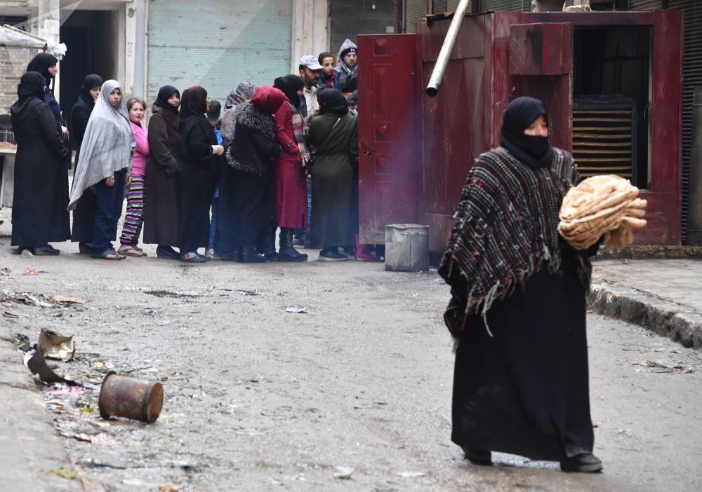 الحياة بعد الحرب، امرأة تحمل خبزا وتسير في أحد شوارع حي صلاح الدين في حلب، سوريا