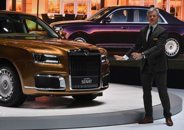 معرض جنيف الدولي للسيارات لعام 2019 - جناح شركة Aurus (أوروس) الروسية والمدير العام للشركة غيرهارد هيلغيرت خلال التقديم
